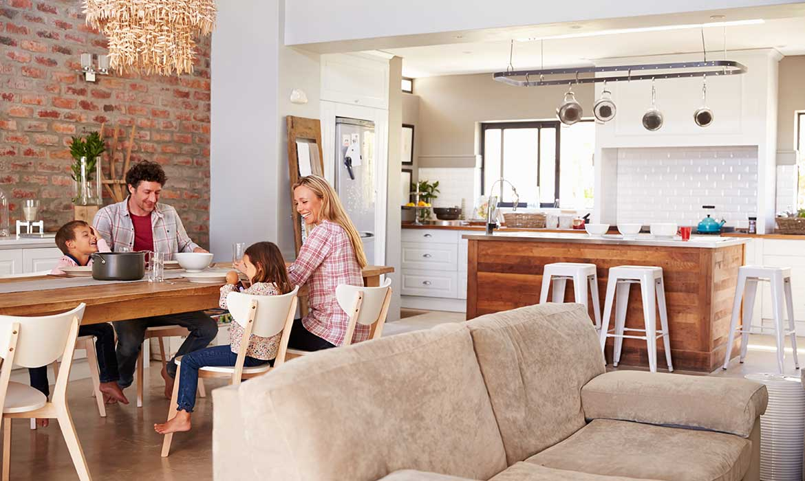 Family enjoying dinner in a large kitchen dining room